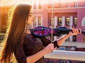 女人對小提琴公園戶外表演音樂。女孩表演爵士樂