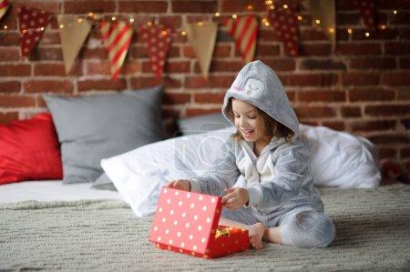 圣诞假期。可爱的女孩 8-9 岁,坐在床上用一个框,在他的手