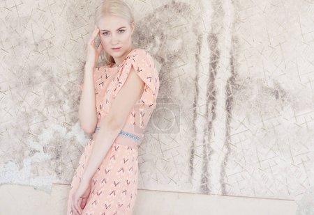 在一条淡粉色裙子金发女性