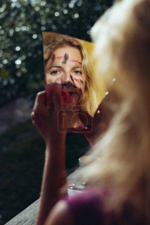 脸上画女人看着破碎的镜子