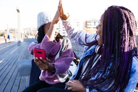 两个美丽的年轻女子在街上握手