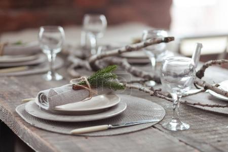 质朴的圣诞配古董银器、 蜡烛和枞树枝的木桌。新年庆祝圣诞晚餐在阁楼内部