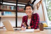 亞洲男性使用筆記本電腦在圖書館寫在筆記本的時候