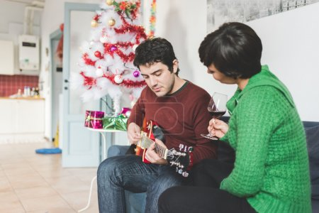 couple sitting on sofa playing guitar