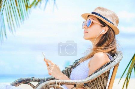 年轻性感的女人,带着耳机在海滩上使用电话_高清图片_邑石网