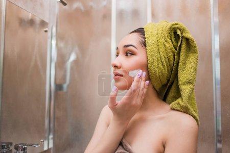 美丽的年轻女子,她脸上应用美容霜治疗_高清图片_邑石网