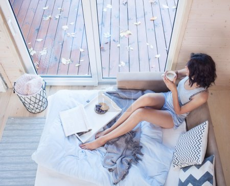 Young beautiful brunette woman with cup of coffee sitting down on the bed
