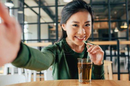 在咖啡馆里喝果汁的女人