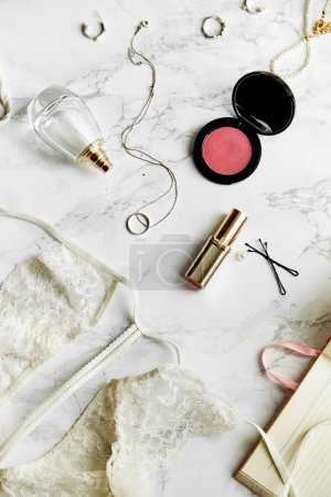 女性蕾丝内衣与香水和口红与珠宝首饰项目白色大理石背景, 美容常规概念