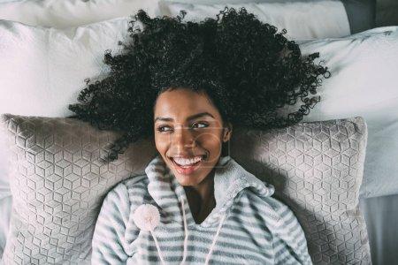 美丽的黑人妇女躺在床上看着相机微笑