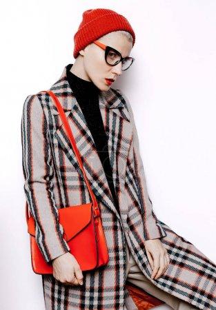 年轻的时髦女学生。时尚格仔复古大衣,