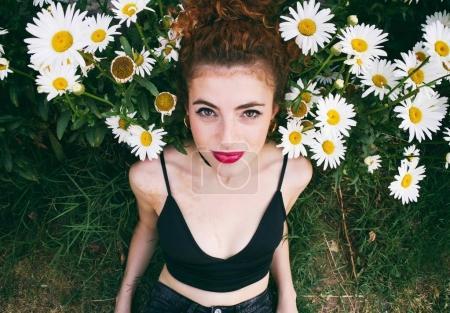年轻红发女人与红色的嘴唇在黑色的衣服摆着雏菊花