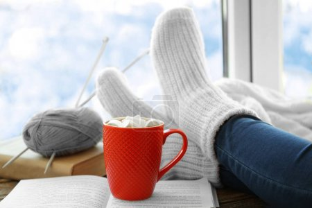 Human legs beside cup of coffee