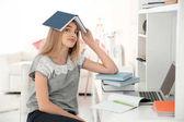 女学生的书在她的头在室内。准备考试