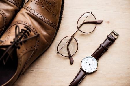 木质表面的棕色鞋子、眼镜和手表