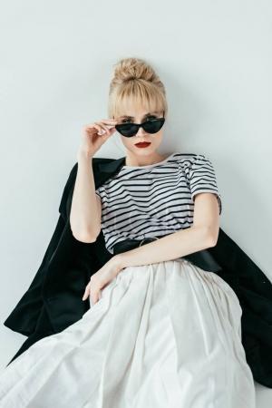 穿着黑白相间的衣服和太阳镜的迷人年轻女子