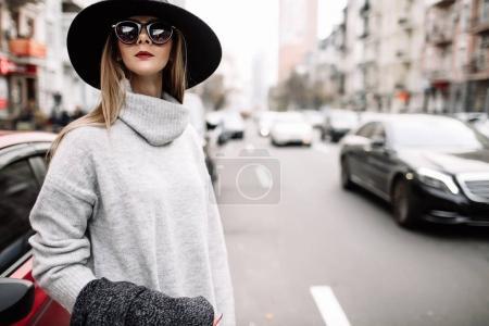 特写肖像一个年轻漂亮的时髦的女人戴着太阳镜。时尚宽边帽的模型