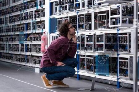 young computer engineer sitting on floor and looking at cryptocurrency mining farm