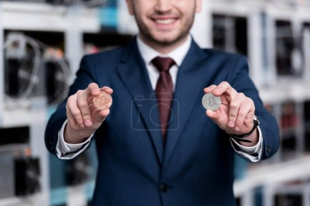 cropped shot of smiling businessman holding bitcoins at cryptocurrency mining farm