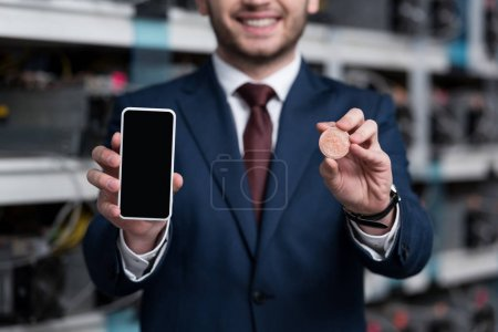 cropped shot of businessman showing smartphone and bitcoin at cryptocurrency mining farm
