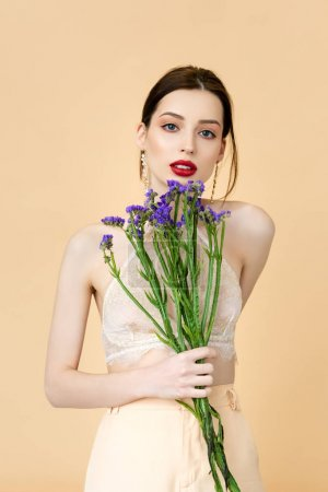 beautiful woman holding purple flowers isolated on beige