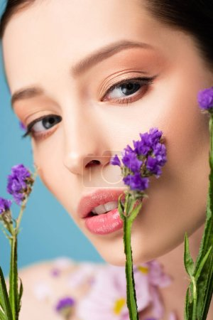 close up of pretty woman looking at camera near blooming flowers isolated on blue