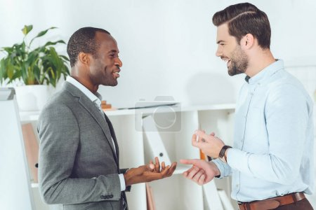smiling african american and caucasian businessmen talking on office
