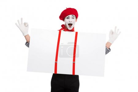 happy mime holding empty board under suspenders and showing ok sign isolated on white