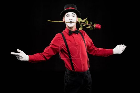 mime holding red rose in mouth and standing with open arms isolated on black