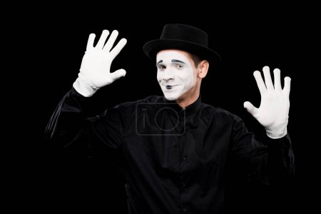 smiling mime performing and touching something isolated on black