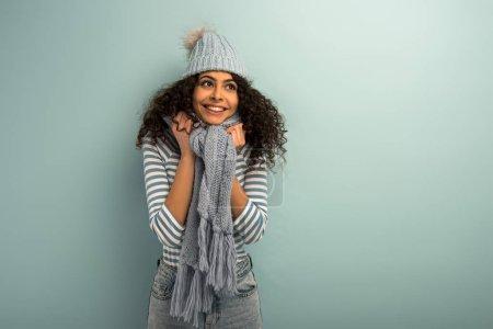 戴着温暖的帽子和围巾的漂亮的双族女孩笑着,把目光投向远方的灰色背景_高清图片_邑石网