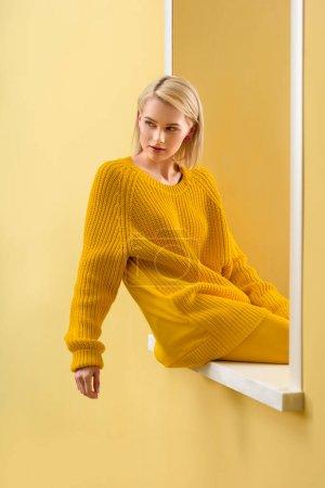 穿着黄色毛衣的时尚金发女郎坐在装饰窗上
