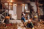 可爱的小男孩和母亲穿着毛衣, 牛仔裤在秋天的时候在房子附近玩毛绒玩具熊。院子里的女人和儿子, 用手电筒点燃, 干落叶, 南瓜.