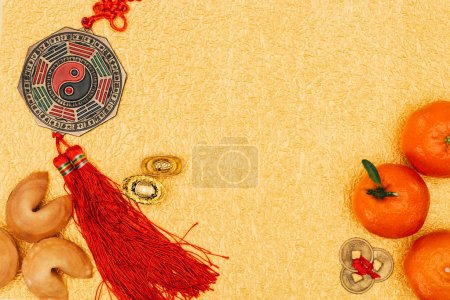 top view of chinese talismans with tangerines and fortune cookies on golden surface, Chinese New Year concept