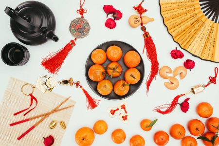 top view of various chinese talimans with tangerines and tea isolated on white, Chinese New Year concept
