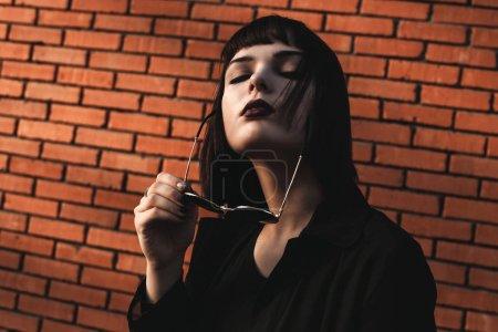 戴着太阳镜的年轻女子画像在砖墙附近