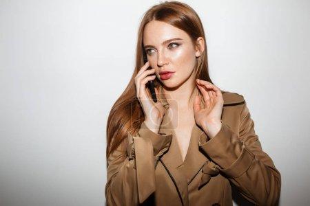 年轻美丽的女士在战壕大衣的肖像站在一旁若有所思地看着一边在她的手机孤立_高清图片_邑石网