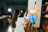 女画家在她的车间里画一幅油画画在画架上