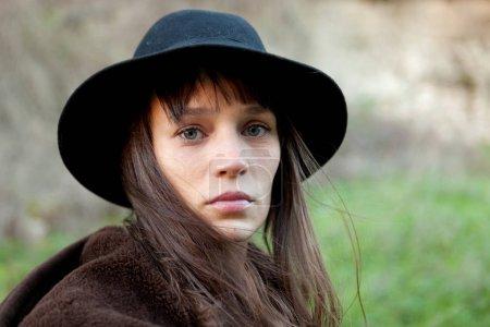 年轻迷人的女人戴着黑色的帽子在农村的肖像, 特写