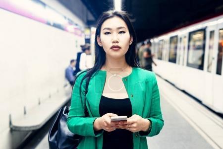 年轻美丽时髦的亚洲女士, 长着深色头发穿长青夹克是看着相机, 而站在一个模糊的平台背景, 而火车是未来的手机