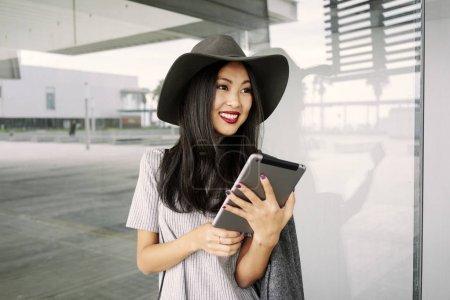 美丽时尚的亚洲妇女与平板摆在现代建筑附近