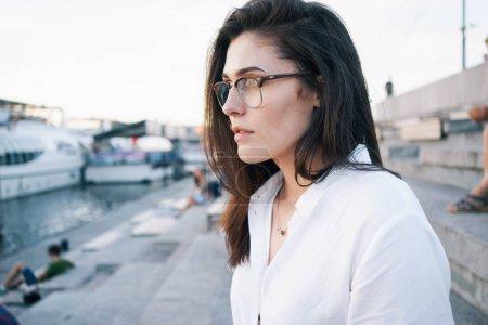 一张照片, 一个美丽的黑发妇女在眼镜穿着白色衬衫摆在城市公园背景