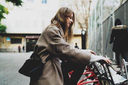 时尚的学生女孩穿着时髦的衣服坐在租用的城市自行车, 并准备骑上