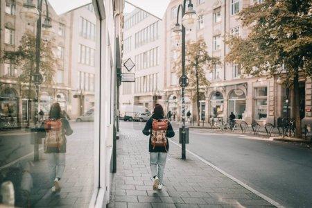带背包的年轻女子穿着运动和休闲在一个城市的蓝色牛仔裤和蓝色毛衣, 并在夏天的商店橱窗反射