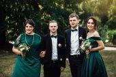 年轻美丽的伴娘和伴郎的肖像在户外婚礼当天