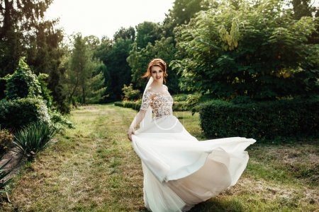 美丽的新娘穿着白色豪华的礼服站在绿色花园