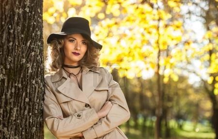奶油色的外套、 长腿与黑色的帽子,在一个秋天的场景中的金发美女。一个非常漂亮的年轻优雅和卷曲的头发在秋天公园构成的性感女人的画像._高清图片_邑石网