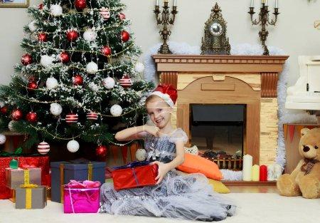 小女孩坐在圣诞树旁与一个大礼物._高清图片_邑石网
