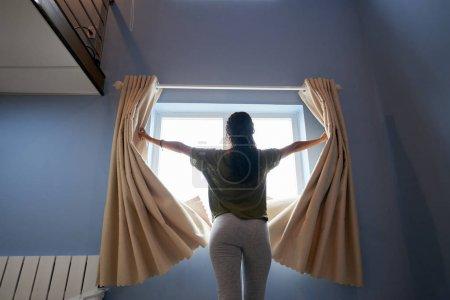 妇女在早晨打开窗帘的背面视图
