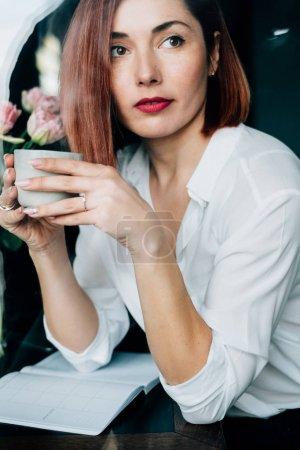 年轻有魅力的女人的照片喝咖啡拿铁